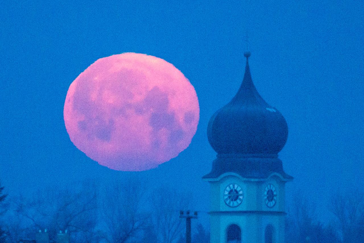 The moon sets behind the parish church of Schoenach near Regensburg, southern Germany, Wednesday morning, Feb. 4, 2015. (AP Photo/dpa, Armin Weigel)