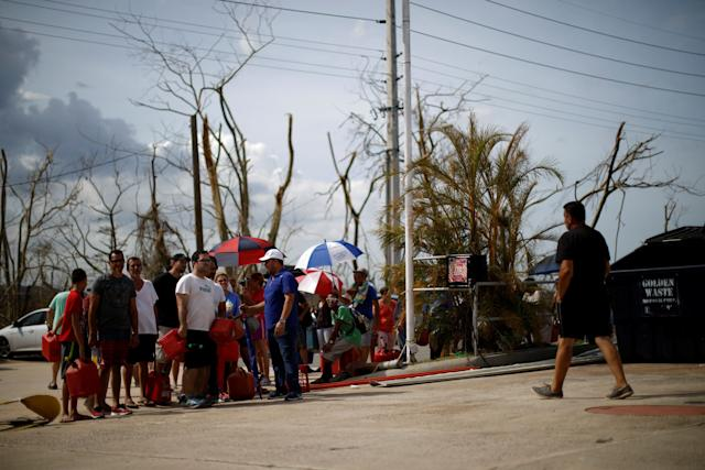People queue to fill containers with gasoline at a gas station after the area was hit by Hurricane Maria in Toa Baja, Puerto Rico.
