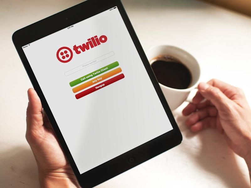 A pair of hands holding a cup of coffee on the right and a tablet with the Twilio client app running on the left.