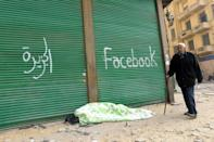 "The slogans of TV channel ""Al-Jazeera"" and social media giant ""Facebook"" are spray-painted at Cairo's Tahrir Square on February 7, 2011"