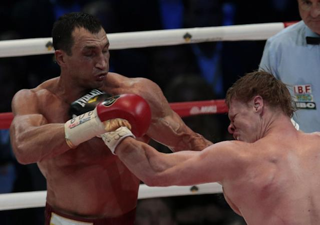 Heavyweight champion Wladimir Klitschko, of Ukraine, left, and Alexander Povetkin, of Russia, hit each other during their bout at the Olympic Stadium, in Moscow, Russia, on Saturday, Oct. 5, 2013. Wladimir Klitschko successfully defended his WBA and IBF titles. (AP Photo/Ivan Sekretarev)