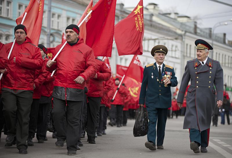 """Demonstrators wearing red and two WWII veterans, right, march in support of Kremlin-backed plans for the Ukrainian province of Crimea to break away and merge with Russia, in Moscow, Saturday, March 15, 2014. Large rival marches have taken place in Moscow over Kremlin-backed plans for Ukraine's province of Crimea to break away and merge with Russia. The marchers belong to a group calling itself the """"Essence of Time,"""" which professes to militate in the interests of social progress in Russia and protect the interests of Russians. (AP Photo/Alexander Zemlianichenko)"""