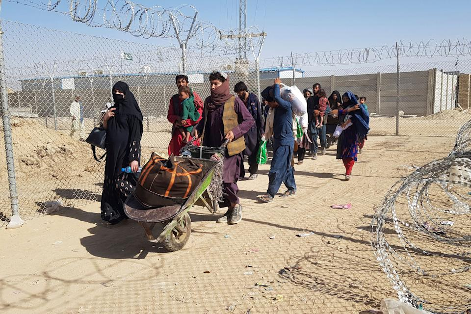 TOPSHOT - Afghan nationals cross the border into Pakistan at the Pakistan-Afghanistan border crossing in Chaman on August 18, 2021. (Photo by - / AFP) (Photo by -/AFP via Getty Images)