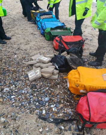 Law enforcement officers stand by holdalls containing cocaine that were washed up on Hopton Beach, near Great Yarmouth, Britain February 9, 2017.  Photograph taken February 9, 2017. National Crime Agency/Handout via Reuters
