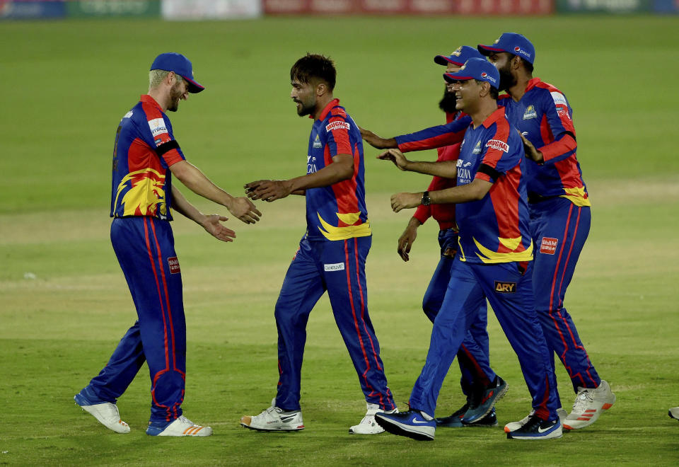 Karachi Kings player Mohammad Amir, second left, celebrates with teammates after won the match in super over during the Pakistan Super League T20 first qualifier cricket match against Multan Sultans at National Stadium in Karachi, Pakistan, Saturday, Nov. 14, 2020. (AP Photo/Fareed Khan)