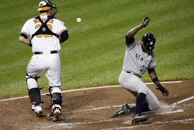 New York Yankees' Alfonso Soriano, right, slides into home plate for a run on a single by Vernon Wells as Baltimore Orioles catcher Matt Wieters tries to get hold of the ball in the third inning of a baseball game, Thursday, Sept. 12, 2013, in Baltimore. (AP Photo/Patrick Semansky)