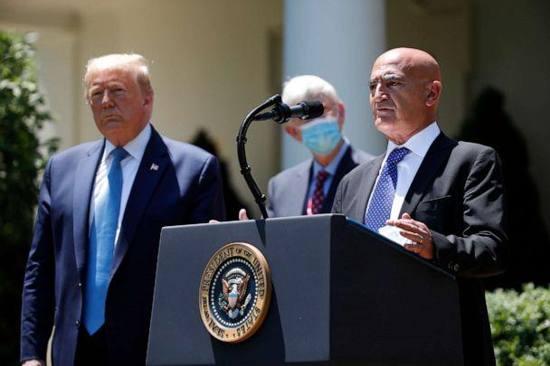 PHOTO: President Donald Trump, left, listens as Moncef Slaoui, a former GlaxoSmithKline executive, speaks about the coronavirus in the Rose Garden of the White House, May 15, 2020, in Washington. (Alex Brandon/AP, FILE)