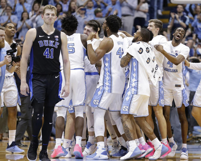 North Carolina players celebrate while Duke's Jack White (41) walks away following an NCAA college basketball game in Chapel Hill, N.C., Saturday, March 9, 2019. North Carolina won 79-70. (AP Photo/Gerry Broome)