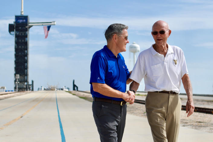 In this Tuesday, July 16, 2019 photo made available by NASA, astronaut Michael Collins, right, speaks to Kennedy Space Center Director Bob Cabana at Launch Complex 39A, about the moments leading up to launch at 9:32 a.m. on July 16, 1969, and what it was like to be part of the first mission to land on the moon. Collins was orbiting in the Command Module, while Neil Armstrong and Buzz Aldrin went to the surface in the Lunar Module. (Frank Michaux/NASA via AP)