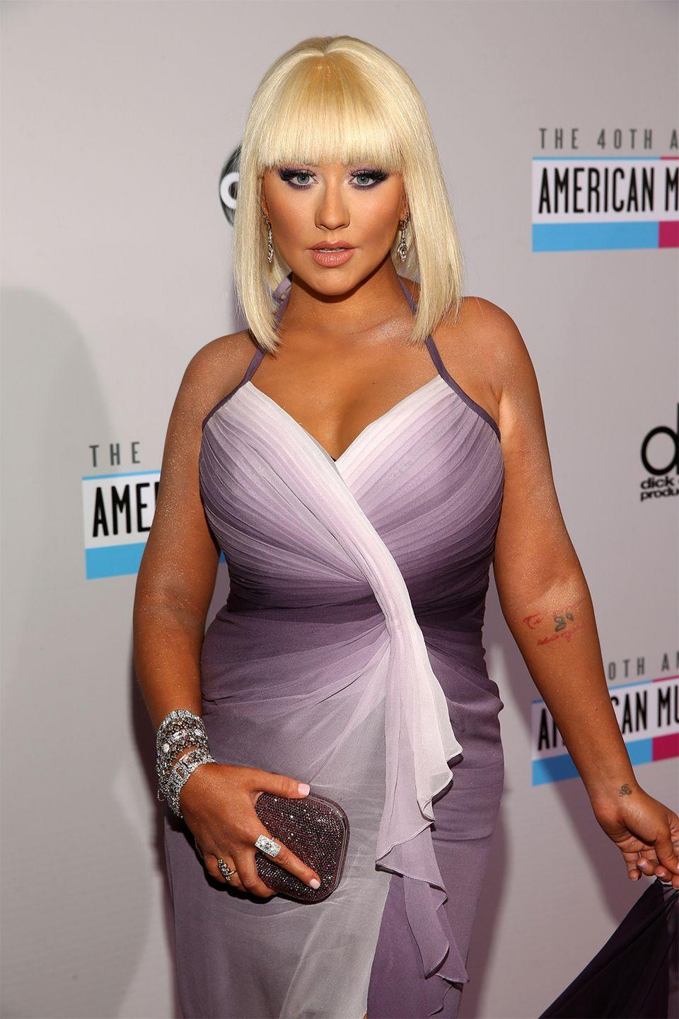 """<p>The singer got inked after she got hitched to Jordan Bratman. For her happily ever tattoo, she chose to have his initials written on her inner arm in Hebrew. However, they filed for divorce in 2010, and Aguilera was left with the ink. Turns out <a href=""""https://www.yahoo.com/entertainment/photos/the-voice-tattoos-the-judges-regret-getting-slideshow/christina-aguilera-photo-1330128363.html"""" data-ylk=""""slk:the combination of characters;outcm:mb_qualified_link;_E:mb_qualified_link;ct:story;"""" class=""""link rapid-noclick-resp yahoo-link"""">the combination of characters</a> she got actually means """"12"""" in Hebrew, not """"JB."""" It seems like Xtina might have lucked out this time.</p>"""