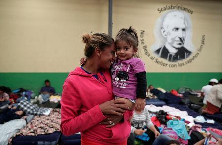 A Honduran migrant, part of a caravan trying to reach the U.S., carries her daughter at a migrant shelter in Guatemala City, Guatemala October 17, 2018. REUTERS/Luis Echeverria