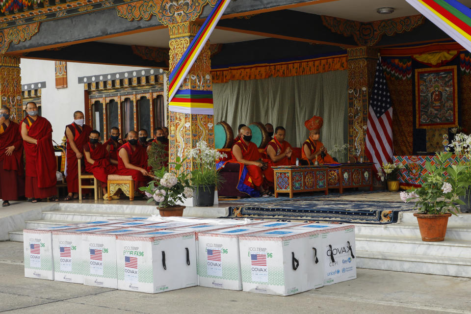 This photograph provided by UNICEF shows monks from Paro's monastic body perform prayers as 500,000 doses of Moderna COVID-19 vaccine gifted from the United States arrived at Paro International Airport in Bhutan, July 12, 2021. The Himalayan kingdom of Bhutan has fully vaccinated 90% of its eligible adult population within just seven days, its health ministry said Tuesday. (UNICEF via AP)