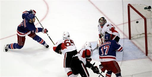 New York Rangers' Dan Girardi, left, scores a goal on Ottawa Senators goalie Craig Anderson, top right, during the second period of Game 7 of a first-round NHL hockey Stanley Cup playoff series on Thursday, April 26, 2012, in New York. (AP Photo/Julio Cortez)