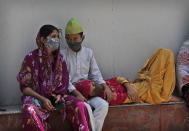 A family waits to receive the body of a person who died due to COVID-19 outside a mortuary, in New Delhi, India, Monday, April 19, 2021. India's health system is collapsing under the worst surge in coronavirus infections that it has seen so far. (AP Photo/Manish Swarup)