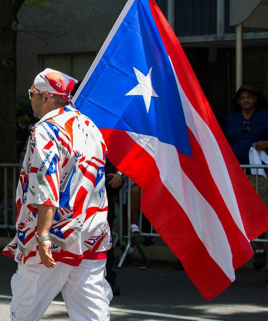 A parade-goer marches with a giant Puerto Rican flag during the 62nd annual Puerto Rican Day Parade on June 9, 2019 in New York, NY. The parade celebrates New York Citys Puerto Rican residents- which make up about 9% of the citys entire population, the largest in Americas major cities. (Photo by Erin Lefevre/NurPhoto via Getty Images)