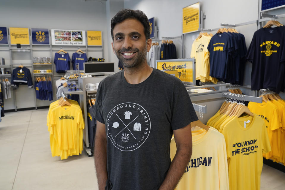 Rishi Narayan, owner of Underground Printing, smiles for a photo in Ann Arbor, Mich., July 7, 2021. Narayan, whose company sells apparel and other products online through its 25 stores around the country, is taking a wait-and-see approach on reaching endorsement deals with college athletes. (AP Photo/Paul Sancya)