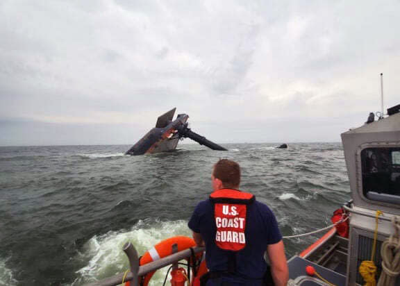 In this photo provided by the U.S. Coast Guard, A Coast Guard Station Grand Isle 45-foot Response Boat-medium boat crew member searches for survivors near the capsized SeaCor Power. The Seacor Power, an oil industry vessel, flipped over Tuesday, April 13, 2021 in a microburst of dangerous wind and high seas. (U.S. Coast Guard via AP)