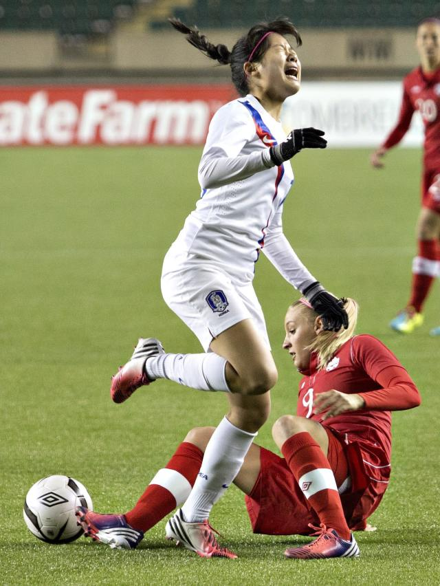 South Korea's Hyunsook Seo (19) is tripped up by Canada's Melissa Busque (9) during the first half of an international friendly soccer match, Wednesday, Oct. 30, 2013, in Edmonton, Alberta. (AP Photo/The Canadian Press, Jason Franson)