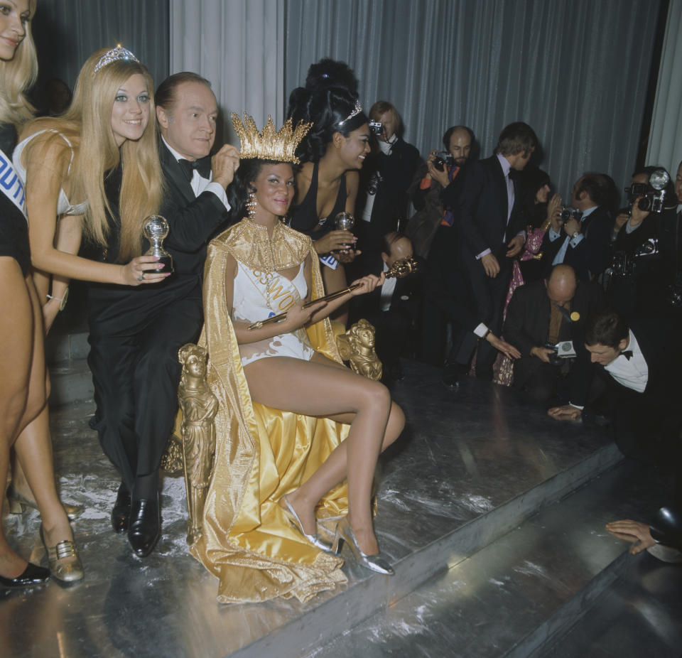 Comedian Bob Hope (1903 - 2003) crowns Jennifer Hosten (Miss Grenada) as the winner of the Miss World 1970 beauty pageant at the Royal Albert Hall in London, 20th November 1970. Also visible are runners-up Jillian Jessup (Miss South Africa, left) and Pearl Jansen (Miss Africa South). (Photo by Peter King/Fox Photos/Hulton Archive/Getty Images)