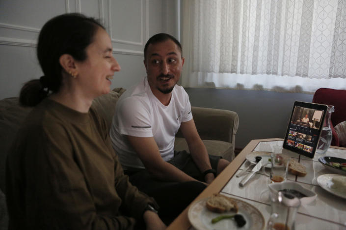 Alparslan Atas, 41, center, and his wife Gulistan, 38, left, laugh over breakfast at their home in Istanbul, while watching on a tablet, Sedat Peker, a Turkish fugitive crime boss on a video, Sunday, June 6, 2021. Sunday is the day the 49-year-old convicted crime ringleader posts the latest installation of his hour-long tell-all videos from his stated base in Dubai that have captivated Turkey and turned the mobster into an unlikely social media phenomenon. The convicted crime ringleader has been dishing the dirt on members of Turkish President Recep Tayyip Erdogan's ruling party. The allegations range from drug trafficking and a murder cover-up to weapons transfers to Islamic militants. (AP Photo/Mehmet Guzel)