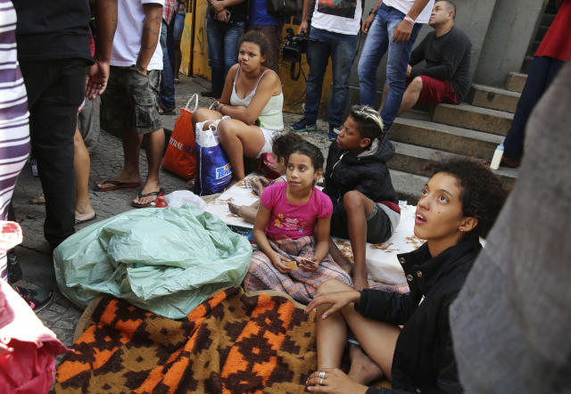 <p>Displaced occupants of a collapsed building sit on the sidewalk in Sao Paulo, Brazil, Tuesday, May 1, 2018. (Photo: Andre Penner/AP) </p>