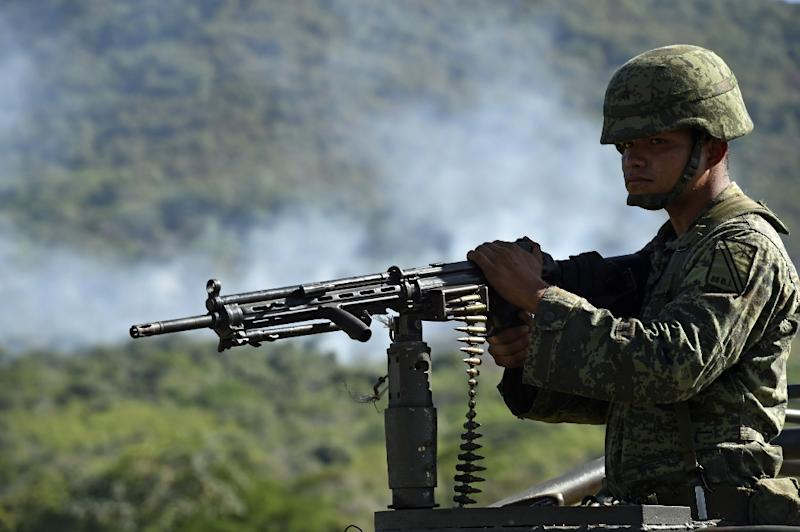 A soldier of the 88 infantry brigade patrols as smoke raises after a military helicopter was shot down in Villa Vieja community, Villa Purificacion, Jalisco State, Mexico on May 2, 2015 (AFP Photo/Yuri Cortez)