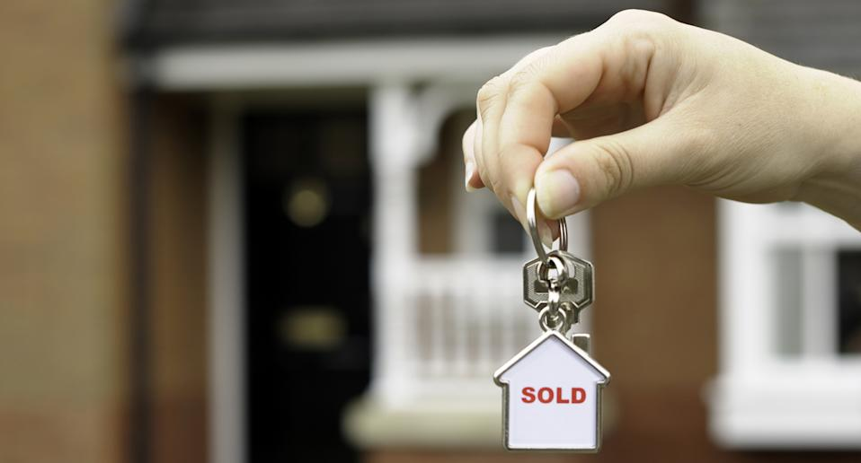 A female holding the house keys to property she just purchased.