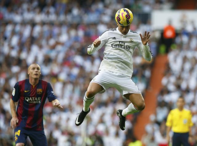 "Real Madrid's Cristiano Ronaldo heads the ball as Barcelona's Jeremy Mathieu looks on during their Spanish first division ""Clasico"" soccer match at the Santiago Bernabeu stadium in Madrid October 25, 2014. REUTERS/Sergio Perez (SPAIN - Tags: SOCCER SPORT TPX IMAGES OF THE DAY)"