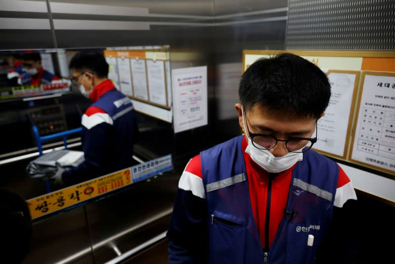 Jeong, a parcel delivery worker for CJ Logistics, holds a package as he rides elevator in Gwangju