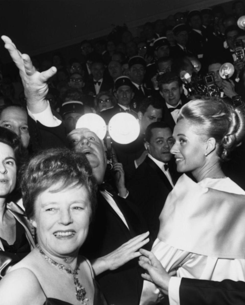 <p>Flashbulbs capture director Alfred Hitchcock raise his arm to the sky next to star Tippi Hedren at the premiere of their thriller, <em>The Birds</em> in 1963. The famed master of suspense makes a cameo in the film, along with his two beloved dogs.</p>