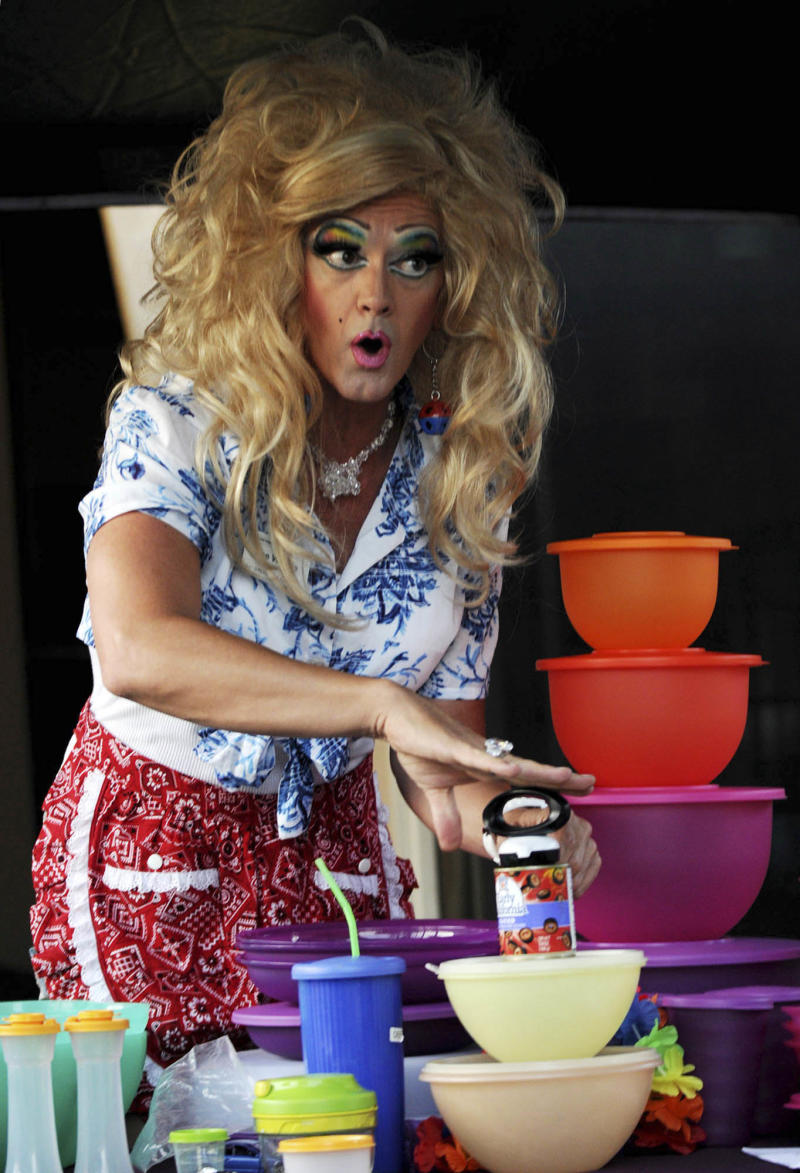 This Friday, Aug. 5, 2011 photo shows Kevin Farrell dressed as Dee W. Ieye selling Tupperware products during a Tupperware party in Bellflower, Calif. Tupperware, it seems, is enjoying a renaissance 65 years after it first hit the market with Wonder Bowls, Bell Tumblers and Ice-Tup molds for homemade frozen treats.  (AP Photo/Garrett Cheen)