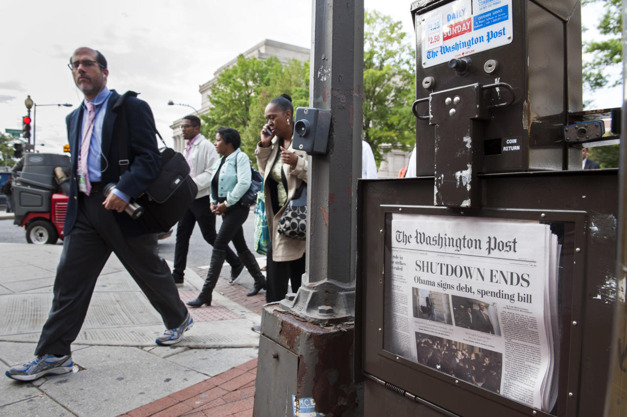 People pass a Washington Post newspaper box as they head to work near Pennsylvania Ave., NW, in Washington, Thursday, Oct. 17, 2013. After 16 days of being off the job, thousands of furloughed federal workers are returning to work now that the government shutdown has been resolved. (AP Photo/Cliff Owen)