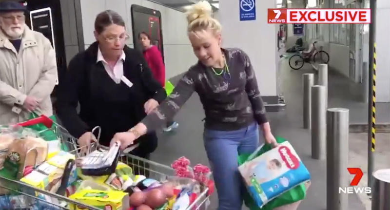 The alleged shoplifter grabs a few items while the Woolworths employee holds the trolley.
