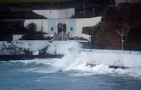 Waves crash on a wall at the port of Angra do Heroismo in Azores
