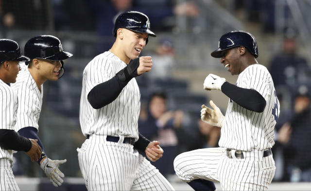 New York Yankees' Didi Gregorius, right, celebrates by dancing on the field with Gleyber Torres, Giancarlo Stanton, and Aaron Judge all of whom scored on his eighth-inning grand slam in a baseball game against the Minnesota Twins in New York, Monday, April 23, 2018. (AP Photo/Kathy Willens)