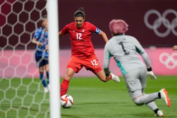 Canada's Christine Sinclair, left, scores her team's lone goal against Japan at the Olympic Games Tokyo 2020 on Wednesday in Sapporo, Japan. The Canadian captain now has 12 goals in 15 matches at the Olympics, having scored in four Olympic tournaments. (Silvia Izquierdo/The Associated Press - image credit)