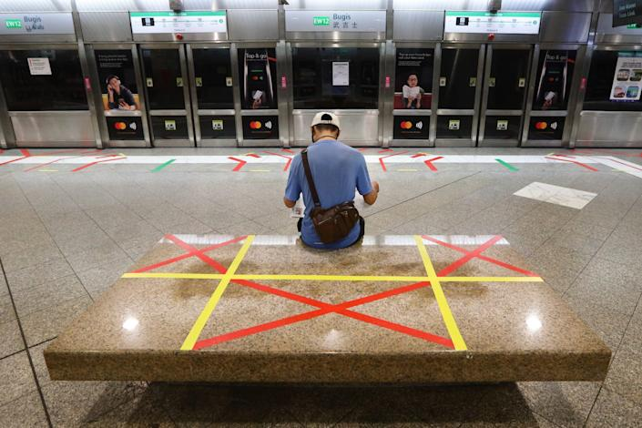 <br>A man reading a newspaper sits on an unmarked safety distancing marker at a train station on April 21, 2020 in Singapore.