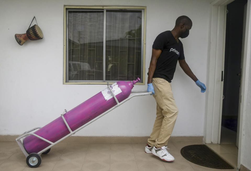 A worker from a private medical service brings oxygen bottles to aid the recovery of a COVID-19 patient, at her home in Lagos, Nigeria on Saturday, Feb. 6, 2021. A crisis over the supply of medical oxygen for coronavirus patients has struck in Africa and Latin America, where warnings went unheeded at the start of the pandemic and doctors say the shortage has led to unnecessary deaths. (AP Photo/Sunday Alamba)