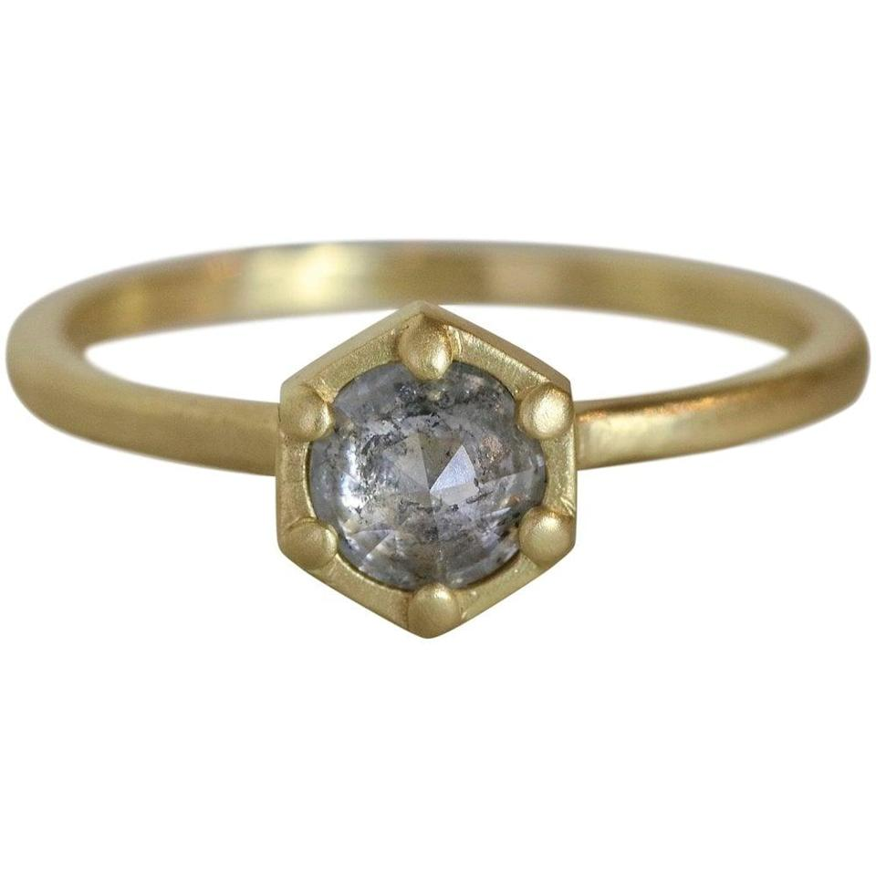 """<p>This distinctive <a href=""""https://www.popsugar.com/buy/Deco-Hex-Diamond-Ring-532651?p_name=Deco%20Hex%20Diamond%20Ring&retailer=sarahswell.com&pid=532651&price=1%2C125&evar1=fab%3Aus&evar9=47015200&evar98=https%3A%2F%2Fwww.popsugar.com%2Ffashion%2Fphoto-gallery%2F47015200%2Fimage%2F47025514%2FHexagons-Deco-Hex-Diamond-Ring&list1=shopping%2Cjewelry%2Crings%2Cengagement%20rings&prop13=mobile&pdata=1"""" rel=""""nofollow noopener"""" class=""""link rapid-noclick-resp"""" target=""""_blank"""" data-ylk=""""slk:Deco Hex Diamond Ring"""">Deco Hex Diamond Ring</a> ($1,125) has the most captivating gray rose-cut diamond set in the middle of a solid recycled gold band.</p>"""