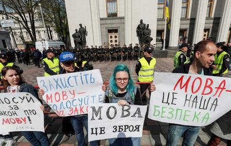 "Activists attend a rally to demand lawmakers vote for a law that grants special status to the Ukrainian language and introduces mandatory language requirements for public sector workers, in front of the parliament building in Kiev, Ukraine April 25, 2019. Banners reads (L-R) ""Vote for the language law"", ""Protect language, vote for the language law"", ""Language is a weapon"", ""Language is our security"".  REUTERS/Gleb Garanich"