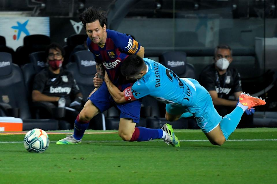 Barcelona's Argentine forward Lionel Messi (L) is tackled by Leganes' Spanish defender Unai Bustinza during the Spanish league football match FC Barcelona against CD Leganes at the Camp Nou stadium in Barcelona on June 16, 2020. (Photo by LLUIS GENE / AFP) (Photo by LLUIS GENE/AFP via Getty Images)