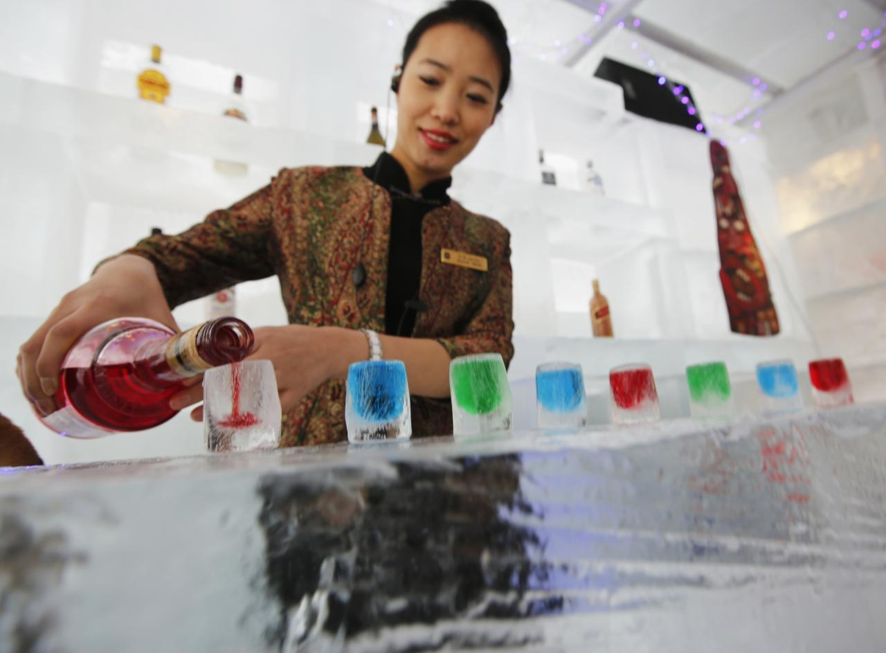 A waitress pours liquor into ice cups on an ice counter during a photo opportunity at the Ice Palace in Shangri-La Hotel in the northern city of Harbin, Heilongjiang province January 6, 2014. The Ice Palace, which is built by ice bricks, is open annually from December to February and attracts visitors during the Harbin Ice and Snow Festival. The temperatures inside the ice building is maintained around -10 degrees Celsius and it consists of bar and hot pot restaurant. REUTERS/Kim Kyung-Hoon (CHINA - Tags: SOCIETY TRAVEL ENVIRONMENT)