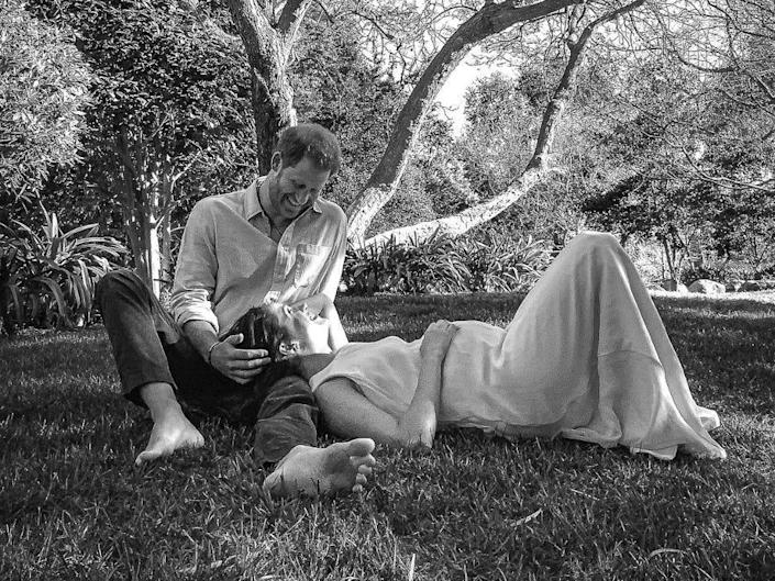 Harry and Meghan pose in a black and white photo under a tree to announce they are expecting a second child.