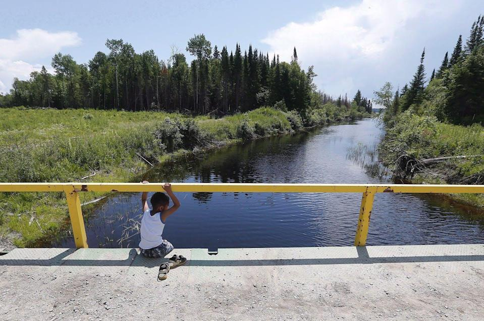 """<span class=""""caption"""">A boy sits on a bridge over a man-made channel in the First Nation of Shoal Lake 40, straddling the Manitoba/Ontario border, in June 2015. Until recently, a boil-water advisory had been in place in the community for more than 20 years despite its relative close proximity to Winnipeg.</span> <span class=""""attribution""""><span class=""""source"""">THE CANADIAN PRESS/John Woods</span></span>"""