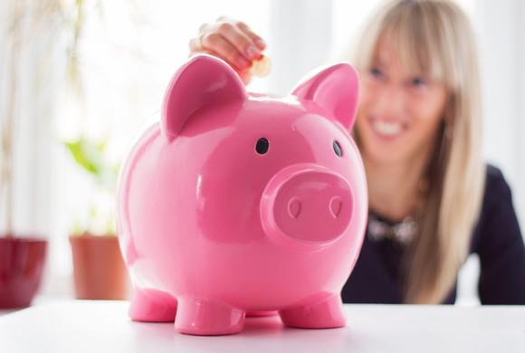 A woman in the background adding a coin to a piggy bank.