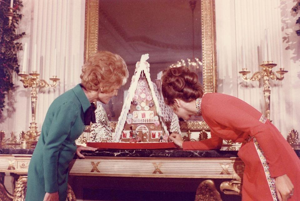 <p>First Lady Pat Nixon and her daughter Julie Nixon Eisenhower admire the first gingerbread house in the White House, based on Hansel and Gretel fairy tale. </p>