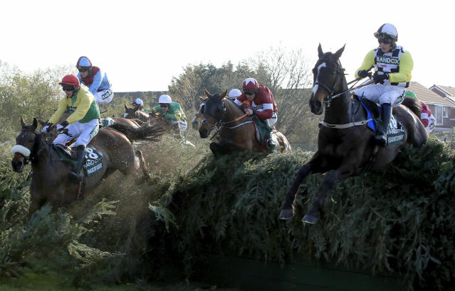 Tiger Roll, center, ridden by jockey Davy Russell to go on to win the Grand National Handicap Chase at the Grand National Horse Racing Festival at Aintree Racecourse, near Liverpool, England, Saturday April 6, 2019. (Peter Byrne/PA via AP)