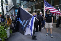 A man holds a Yad Yamin #Fightback flag along with an Israeli flag as he stands next to another man with an American flag as they joined protesters outside the offices of New York Gov. Andrew Cuomo, Thursday, Oct. 15, 2020, in New York. Three Rockland County Jewish congregations filed a lawsuit Wednesday accusing Gov. Andrew Cuomo of engaging in a streak of anti-Semitic discrimination with a crackdown on religious gatherings. The Manhattan federal court lawsuit says Cuomo has made numerous discriminatory statements about the Jewish Orthodox community. (AP Photo/Kathy Willens)