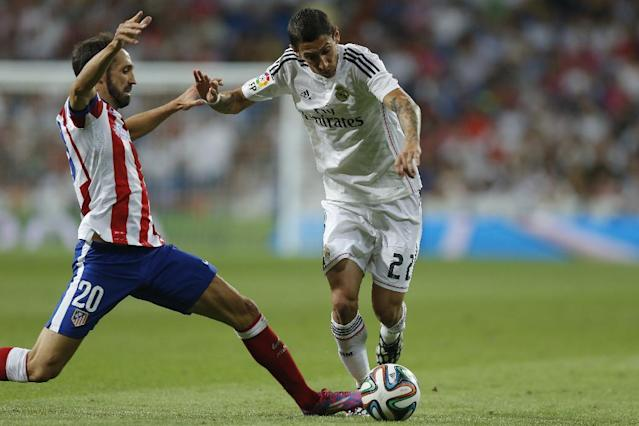 Real Madrid's Angel Di Maria, right, duels for the ball with Atletico Madrid's Juan Fran during a Spanish Super Cup soccer match at Santiago Bernabeu stadium in Madrid, Spain, Tuesday, Aug. 19, 2014 . (AP Photo/Daniel Ochoa de Olza)