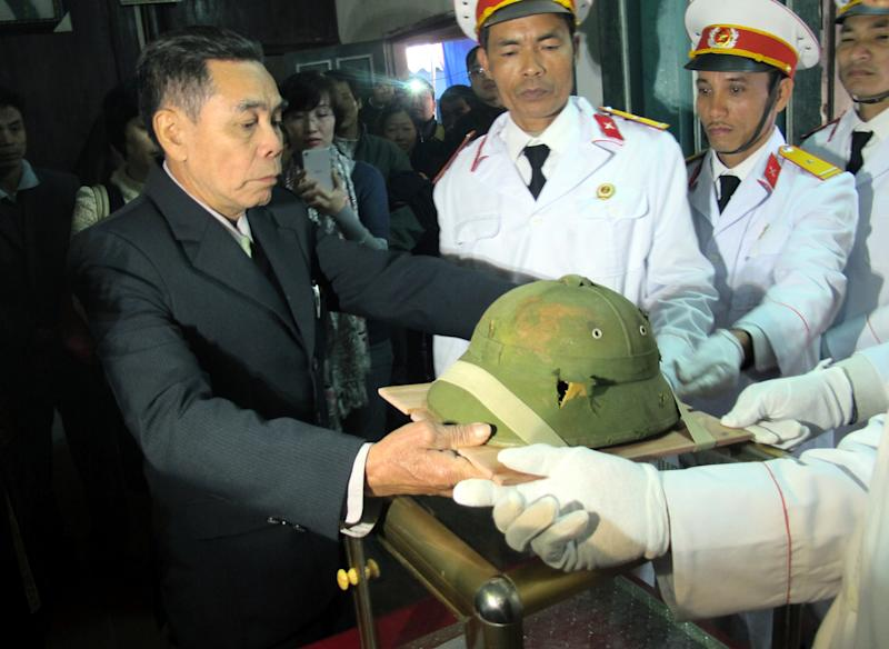 A helmet belonging to slain North Vietnamese soldier Bui Duc Hung, who was killed in the war, is handed over to Bui Dinh Hoe, left, a relative of Hung, in Huong Non village, northern Phu Tho province, Vietnam on Tuesday, Jan. 14, 2014. The helmet, which had been kept as a war souvenir by an American veteran for 46 years, was returned to Hung's family. (AP Photo/Tran Van Minh)